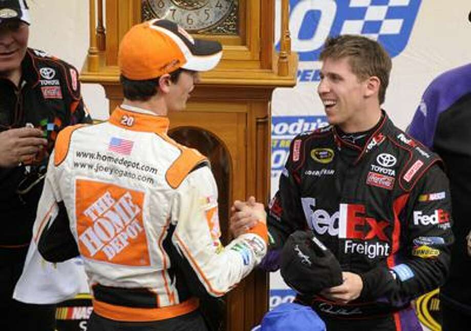 Denny Hamlin, right, shakes the hand of teammate Joey Logano in victory lane after Hamlin won the Goody's 500 NASCAR Sprint Cup Series auto race at Martinsville Speedway in Martinsville, Va., Monday. (Associated Press) Photo: AP / FR59093 AP