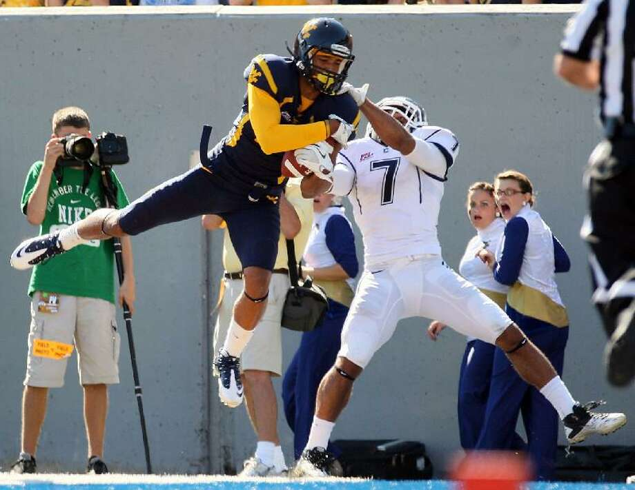 """ASSOCIATED PRESS West Virginia wide receiver Bradley Starks (2) makes a touchdown catch over Connecticut's Dwayne Gratz (7) during the second half of their game on Saturday in Morgantown, <a href=""""http://W.Va"""">W.Va</a>. UConn lost 43-16."""