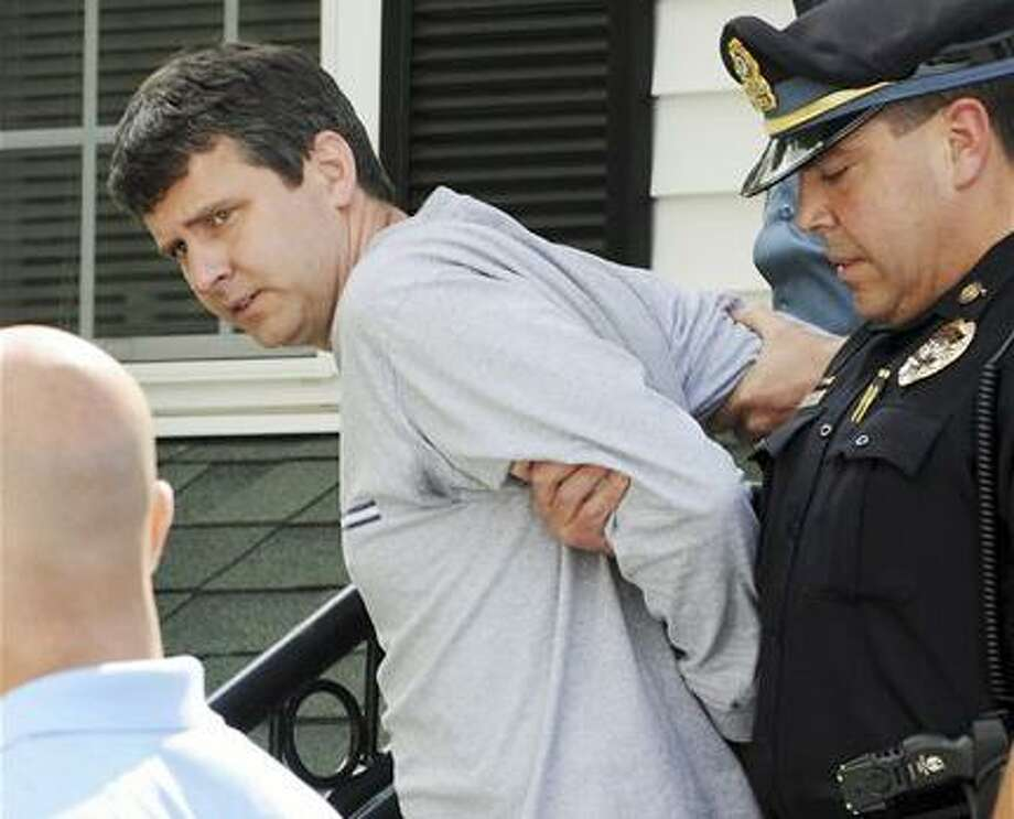 Thomas Mortimer IV, center, is led from the police station by (AP) Police Chief James Palmeri, right, after he was arrested Thursday in Bernardston, Mass. Mortimer is charged with four counts of murder in the death of his wife, two children and mother-in-law, found dead in their home Wednesday in Winchester, Mass. Photo: AP / FR45033 AP