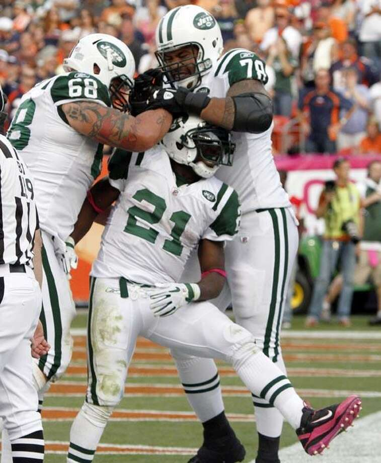 New York Jets running back LaDainian Tomlinson (21) is congratulated by teammates Matt Slauson (68) and Wayne Hunter (78) after scoring the go-ahead touchdown against the Denver Broncos during the fourth quarter of an NFL football game Sunday in Denver. The Jets won 24-20. (AP Photo/Barry Gutierrez) Photo: AP / FR170088 AP
