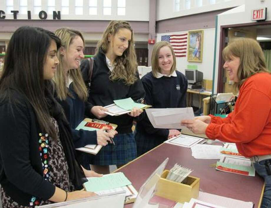Mercy students Maschal Mohiuddin, Lindsey Krupa, Victoria Piscatelli and Erin Wolter receive their instructions from Debbie Shekosky, Chair of the Lawrence School Science Fair.