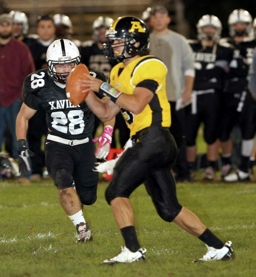 Xavier's Craig Ryan welcomes Amity quarterback Tyler Vallie in Thursday's football game. Xavier won, 49-7. / a