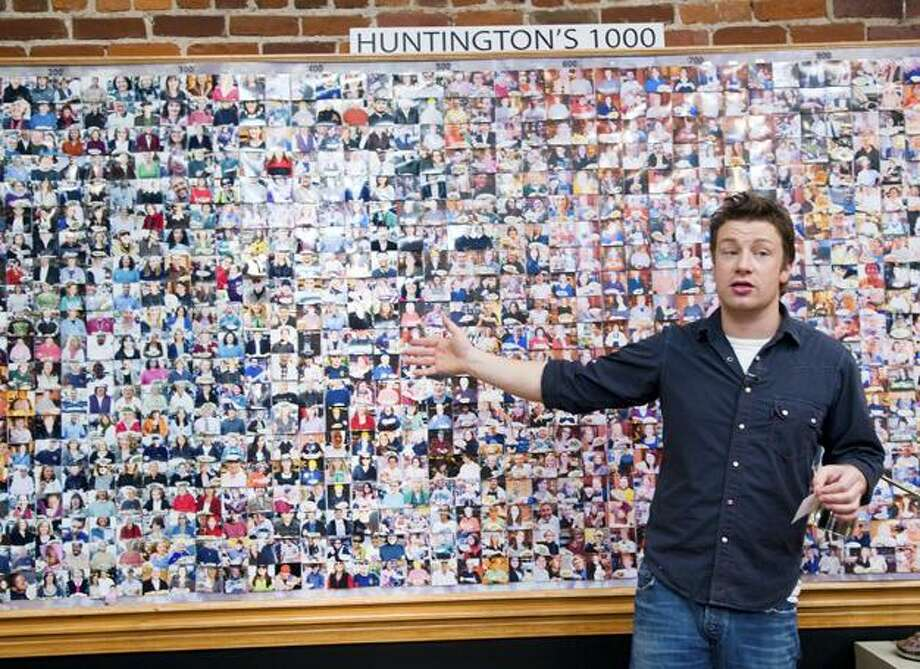 """In this publicity image released by ABC, chef and TV personality Jamie Oliver stands in front of a board with photos of residents of Huntington, W. Va., during the taping of his reality series, """"Jamie Oliver's Food Revolution,"""" in Huntington, W. Va., airing today on ABC. (AP) Photo: AP / © 2010 American Broadcasting Companies, Inc. All rights reserved."""