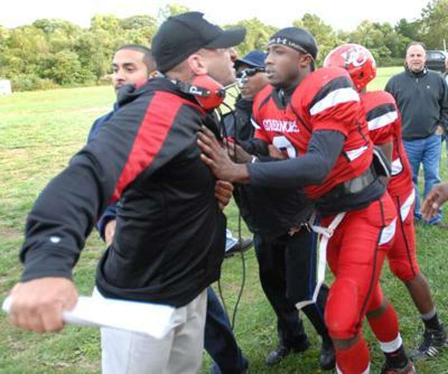 Wilbur Cross High School head football coach John Acquavita, left, is held back by Cross player Aaron Gass and others as an agitated Aquavita yells at Mike Ecke, Cheshire head football coach Mark Ecke's brother, during a disturbance between Aquavita and Ecke at halftime of Cross' 18-14 win over Cheshire Friday at Cross High School. Bystanders said an  exchange of words between the two men led to the disturbance. (Peter Hvizdak/Register)