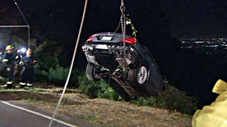 This image taken from video and provided by KTLA-TV shows Charlie Sheen's silver Mercedes S600  being pulled from a cliff at Mulholland Drive near Santa Monica, Calif., Tuesday.  For the second time in five months a vehicle belonging to Sheen has been stolen and sent over a cliff near his home.(AP) Photo: ASSOCIATED PRESS / KTLA