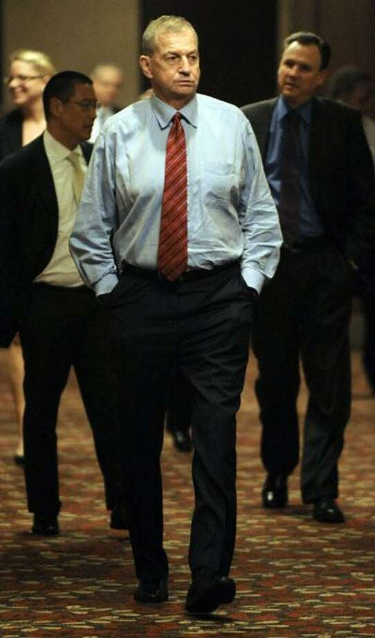 University of Connecticut men's basketball coach Jim Calhoun walks in a hotel hallway as an NCAA infractions committee takes a break in Indianapolis, Friday. (AP) Photo: ASSOCIATED PRESS / FR64984 AP