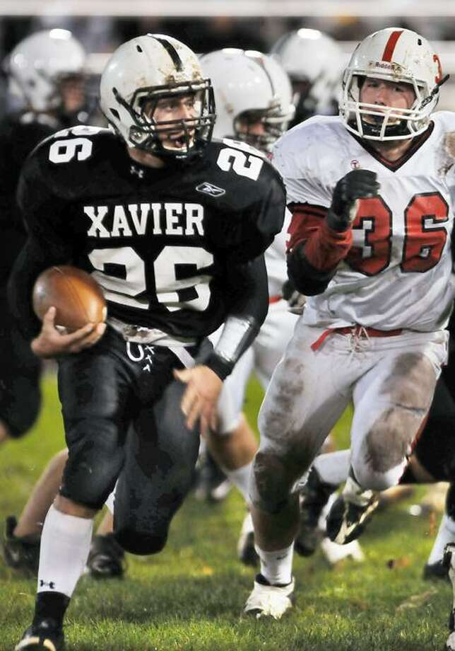 Fairfield Prep's Colin Cinder has an eye on Xavier's Mike Mastrioanni as he carries the ball Friday night at Palmer Field. (Catherine Avalone / TheMiddletownPress