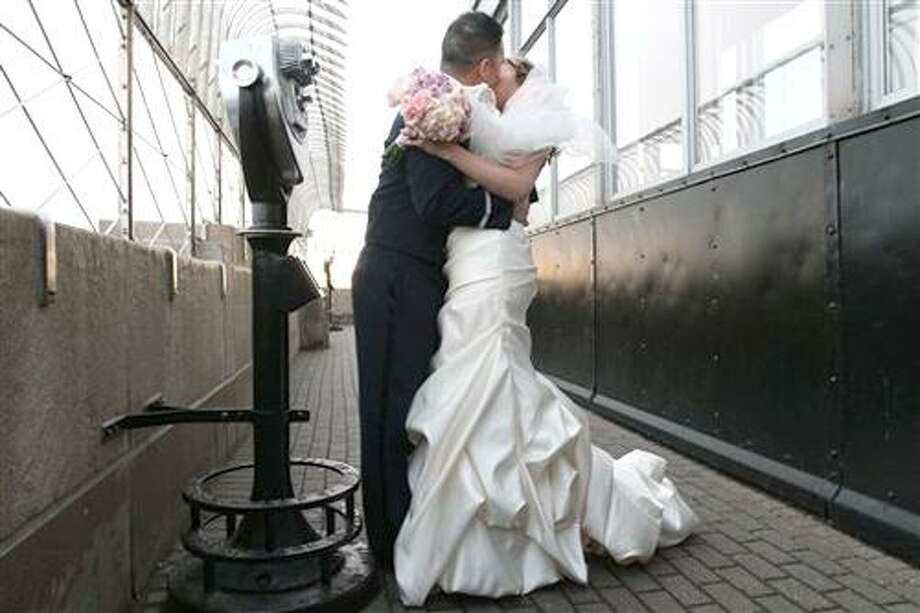 "Newlyweds Air Force Captain John Wu, left, and Stephanie Hull, both from Louisville, Ky., kiss as they pose for photographers after being wed Monday Feb. 14, 2011 on the 86th floor of the Empire State Building in New York. The couple were one of 14 couples from around the country exchanging vows atop the Empire State Building during the 17th Annual Empire State Building and <a href=""http://TheKnot.com"">TheKnot.com</a> Valentine's Weddings Event.  Hull and Wu were the event's grand prize winners.  (AP Photo/Tina Fineberg) Photo: ASSOCIATED PRESS / AP2011"