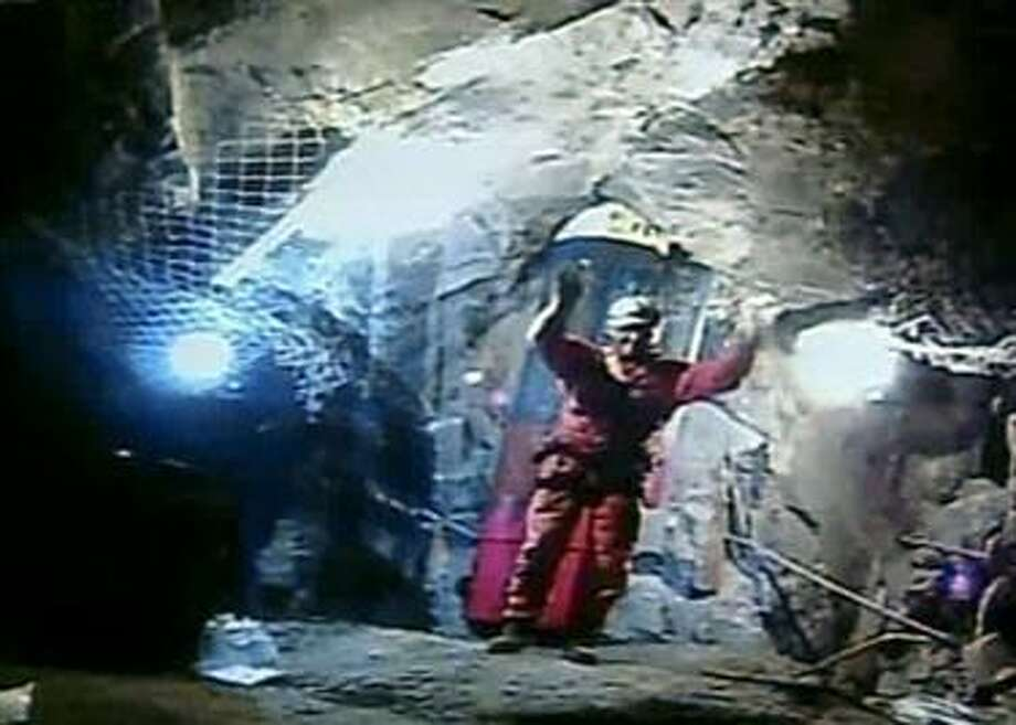In this screen grab taken from video, Manuel Gonzelez, the last of six rescue workers who talked the 33 trapped miners through the final hours, takes a bow inside the San Jose Mine near Copiapo, Chile, before ascending to the surface Wednesday. (AP Photo) Photo: AP / APTN