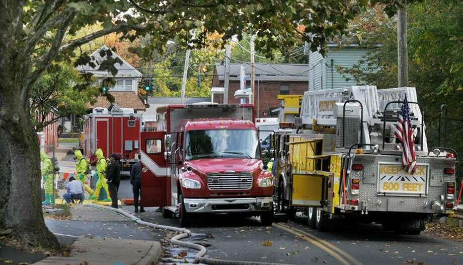 """The Middletown Press  10.14.10  Battalion Chief Larry Anderson of the Middletown Fire Department helps a firefighter suit up in hazmat gear to remove a 10-gallon bucket of strange liquid found by maintenance staff from Wilcox Apartments while cleaning the banks of a brook behind the complex at 309 South Main Street in Middletown Thursday. To buy a glossy print of this photo and more, visit <a href=""""http://www.middletownpress.com"""">www.middletownpress.com</a> Firefighters and emergency personnel are on hand after a mysterious substance was located in a ravine behind the Wilcox Apartment complex at 309 South Main St. Thursday.Officials said a 911 call was placed just before noon Thursday. Middletown police and firefighters were dispatched to the scene where they found a 5-pound bucket filled with a substance yet to be identified. When the con / TheMiddletownPress"""