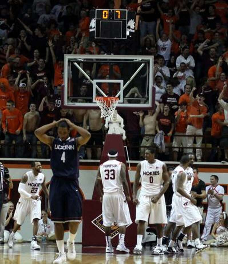 Connecticut's Jamal Coombs-McDaniel (4) walks away as Virginia Tech players celebrate a defensive stop and foul with less than a second left in a second-round NIT college basketball game in Blacksburg, Va., Monday. (Associated Press) Photo: ASSOCIATED PRESS / AP2010