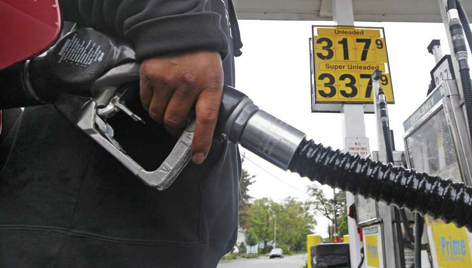 A gas station attendant fills up an automobile's tank with the gallon price of $3.17 in Wakefield, Mass., Tuesday. Oil tumbled to below $76 a barrel Tuesday as fears intensified that Greece may not be able to crawl out from beneath a mountain of debt without defaulting.(AP Photo/Charles Krupa) Photo: AP / AP