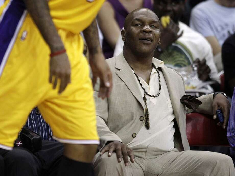 In this Oct. 13, 2010, file photo, Mike Tyson watches an NBA preseason basketball game between the Los Angeles Lakers and the Sacramento Kings in Las Vegas. Tyson will be heading to China in December to help promote boxing there. (AP Photo/Julie Jacobson, File) Photo: AP / AP