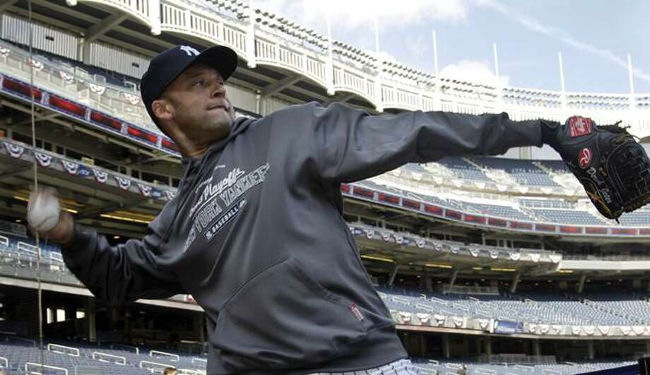 New York Yankees shortstop Derek Jeter tosses in the area behind home plate during a baseball workout at Yankee Stadium in New York, Tuesday. The Yankees face the Texas Rangers Friday in the American League Championship. (AP Photo/Kathy Willens) Photo: AP / AP