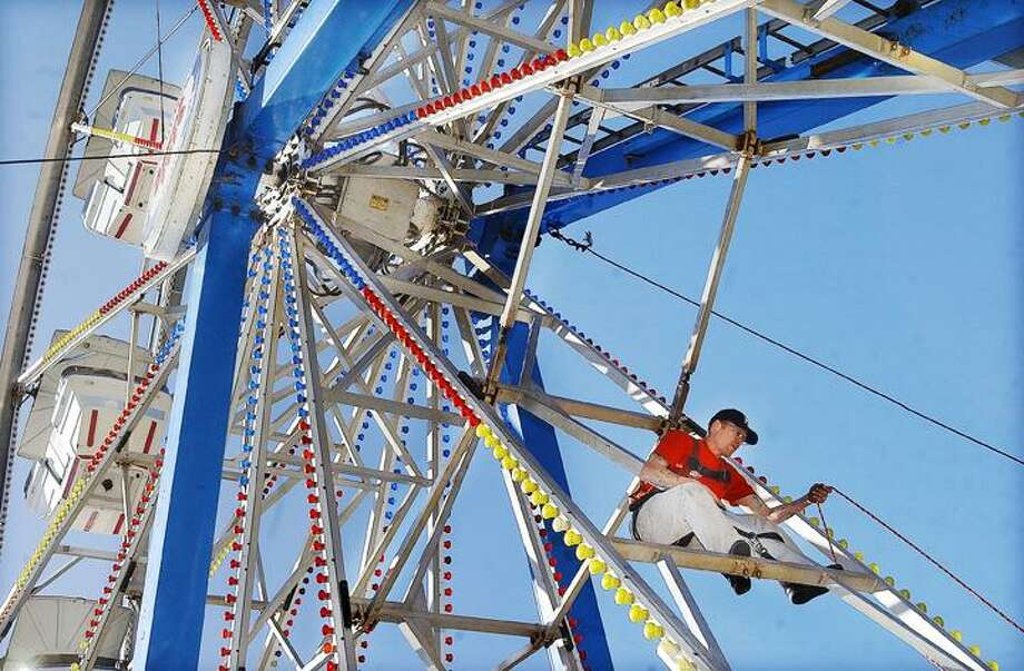"""James Hulett, of Waterbury, adjusts the rope attached to his harness so he can continue to tighten up a brace bar on the Century Wheel at Coleman's Carnival. """"This is the final step before inspection, gotta make it safe for the public,"""" Hulett said.    (Catherine Avalone"""