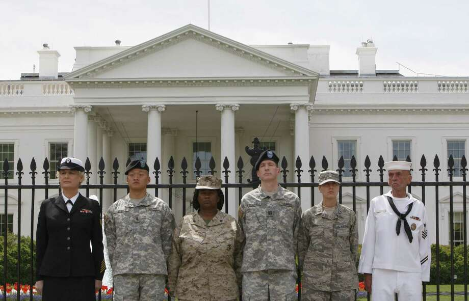 "FILE - In this Tuesday, April 16, 2010 picture, from left, Petty Officer Autumn Sandeen,  Lt. Dan Choi, Cpl. Evelyn Thomas, Capt. Jim Pietrangelo II, Cadet Mara Boyd and Petty Officer Larry Whitt, stand together after they handcuffed themselves to the fence outside the White House in Washington during a protest for gay rights.  A federal judge issued a worldwide injunction Tuesday stopping enforcement of the ""don't ask, don't tell"" policy, ending the military's 17-year-old ban on openly gay troops.   U.S. District Judge Virginia Phillips declared the law unconstitutional after a two-week nonjury trial on the case in federal court in Riverside.  U.S. Department of Justice attorneys have 60 days to appeal. Legal experts say they are under no legal obligation to do so and could let Phillips' ruling stand.  (AP Photo/Pablo Martinez Monsivais) Photo: ASSOCIATED PRESS / AP"