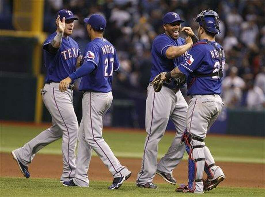 Texas Rangers catcher Mike Napoli, right, congratulates Nelson Cruz, as Leonys Martin (27) congratulates  Josh Hamilton,left,  at the end of  Game 3 of baseball's American League division series against the Tampa Bay Rays, Monday Oct. 2011 in St. Petersburg, Fla. The Rangers won 4-3 to lead the series 2-1. (AP Photo/Lynne Sladky) Photo: AP / AP