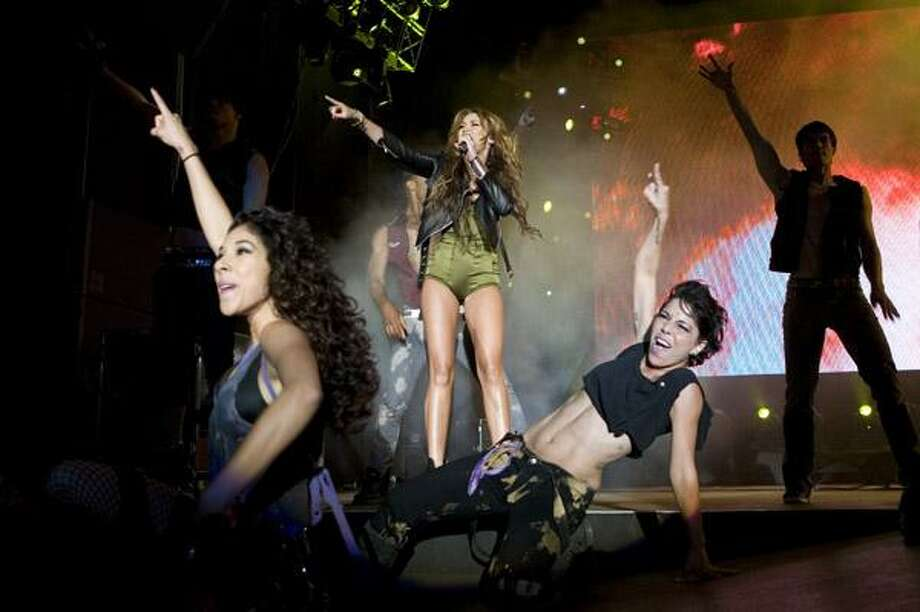 American singer and actress Miley Cyrus, background center, performs during her concert at the Rock in Rio music festival Saturday, May 29, in Lisbon. (AP) Photo: ASSOCIATED PRESS / AP2010