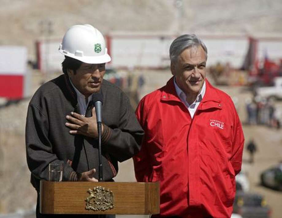 Bolivia's President Evo Morales, left, speaks during a joint news conference with his Chilean counterpart Sebastian Pinera next to the site where the 33 trapped miners are being rescued at the San Jose gold and copper mine near Copiapo, Chile, Wednesday, Oct. 13, 2010. (AP Photo/Jorge Saenz) Photo: AP / AP