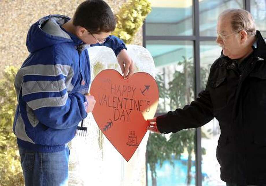 Special to the Press  02.12.11  Nicholas Follacchio of Middletown and his grandson Michael Perry of Rocky Hill work on an ice sculpture of a heart for Valentines Day outside the River's Edge Saturday morning.  Residents watched from the warmth of the lobby. / ©2011 Steve McLaughlin