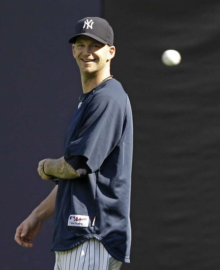 New York Yankees pitcher A.J. Burnett laughs as a ball comes his way during a baseball workout at Yankee Stadium in New York, Tuesday. The Yankees face the winner of the Tampa Bay Rays-Texas Rangers division series in the American League Championship. (AP) Photo: ASSOCIATED PRESS / AP
