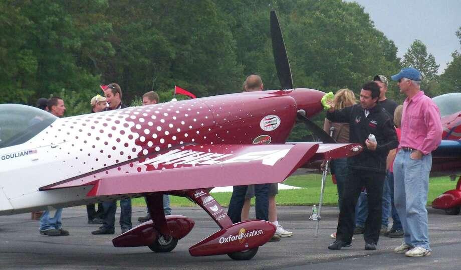Michael Goulian, left, aerobatic aviator/ Red Bull Racer, polishes his plane as he talks to an attendee (Photo by Jonetta Badillo)