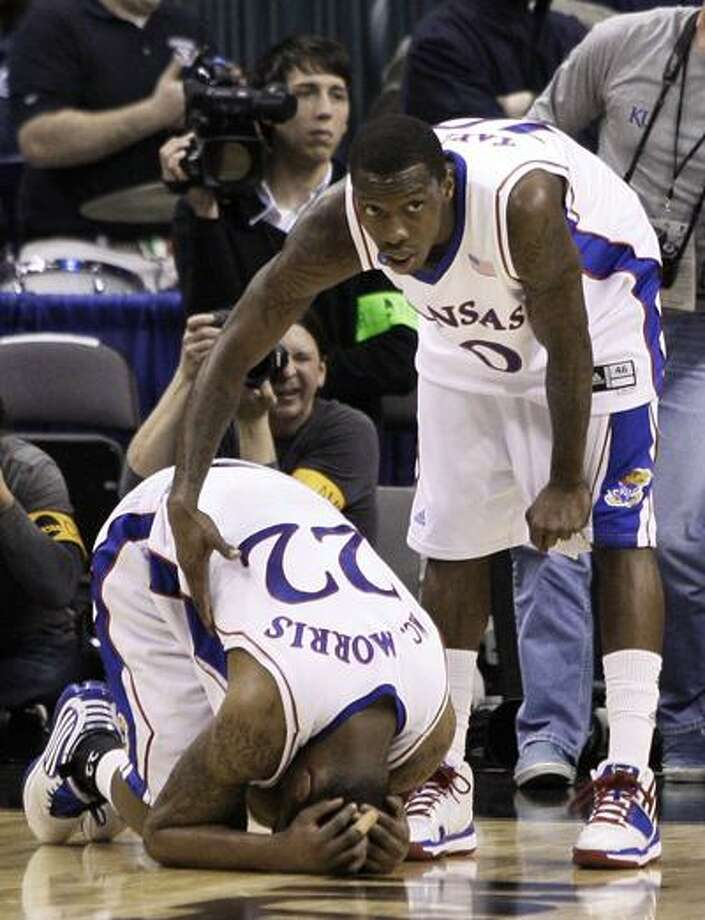 Kansas guard Tyshawn Taylor, right, consoles Kansas forward Marcus Morris (22) after their 69-67 loss to Northern Iowa in an NCAA second-round college basketball game, Saturday. (Associated Press) Photo: ASSOCIATED PRESS / AP2010