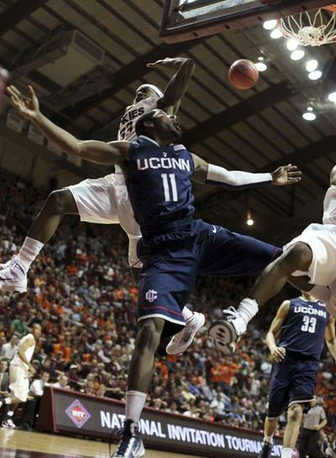 Connecticut's  Jerome Dyson (11) has his shot bounce off the rim in front of Virginia Tech's J.T. Thompson, left, during the first half of an NIT college basketball game in Blacksburg, Va., Monday. (Associated Press) Photo: AP / The Roanoke Times