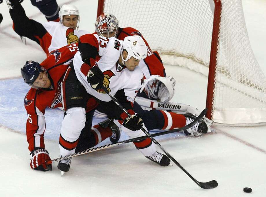 Washington Capitals defenseman Jeff Schultz (55) is knocked over by Ottawa Senators right wing Jarkko Ruutu (73), of Finland, as they struggle for control of the puck during the third period of an NHL hockey game in Washington on Monday. The Capitals won 3-2 in overtime. (AP Photo/Jacquelyn Martin) Photo: AP / AP