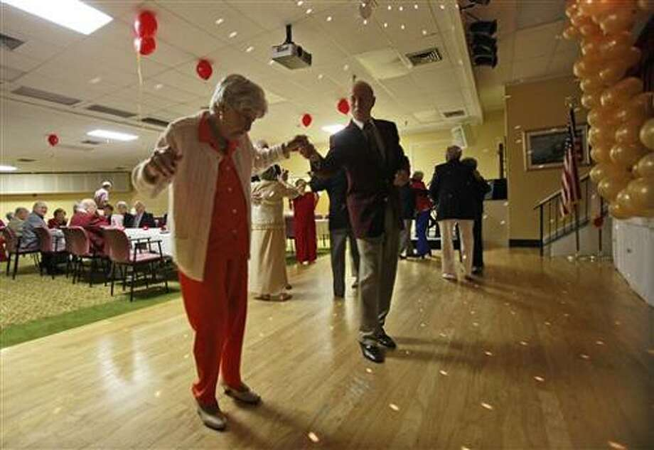 ** ADVANCE FOR MONDAY FEB. 14, 2011 AND THEREAFTER **  In this Feb. 8, 2011 photo Hewitt Bruce, center, dances with Betty Fisch, left, at Edgewater Pointe Estates retirement community in Boca Raton, Fla. Women often so greatly outnumber men in retirement communities that Valentine's Day can be a lonely time. But one development has found a solution to its perennial shortage of men at its dances: They're importing them. (AP Photo/Wilfredo Lee) Photo: AP / AP