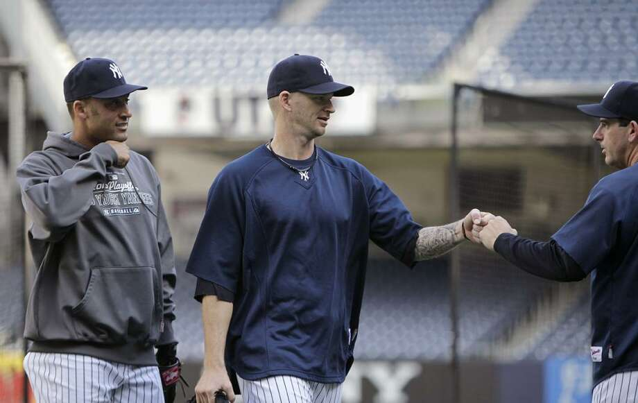 New York Yankees starting pitcher A.J. Burnett, center, bumps fists with third base coach Rob Thomson as he and shortstop Derek Jeter, left, leave the field after a baseball workout at Yankee Stadium in New York, Tuesday. The Yankees face the winner of the Tampa Bay Rays-Texas Rangers division series in the American League Championship. (AP Photo/Kathy Willens) Photo: AP / AP