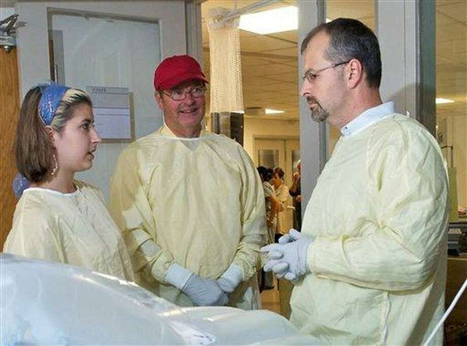 In this undated photo provided by Brigham and Women's Hospital, Steve Nash, center, brother of Charla Nash, and Charla's daughter Briana, left, speak with surgeon Bohdan Pomahac, MD, right, in Charla's room at the hospital in Boston. Charla Nash underwent a full face transplant more than two years after she was mauled and blinded by the chimpanzee. (AP Photo/Brigham and Women's Hospital) Photo: AP / Brigham and Women's Hospital