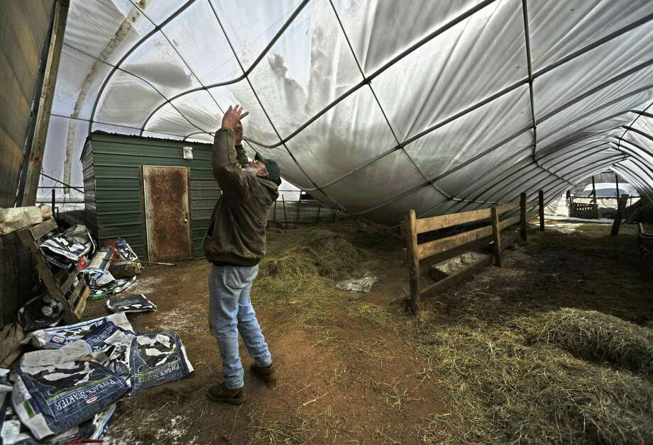 In this photo from last Friday, Joe Greenbacker, a partner at Brookfield Farm, points out damage to a hoop barn on his farm from heavy snow conditions in Durham, Conn.  Greenbacker said there were thirty calves inside at the time collapse, killing one. Connecticut agriculture officials say back-to-back snowstorms and a recent ice storm have brought down the roofs of more than 130 barns, greenhouses, equipment buildings and other farm buildings. More than a dozen dairy cows, two horses and a calf have been killed in building collapses. (AP Photo/Jessica Hill) Photo: ASSOCIATED PRESS / AP2011