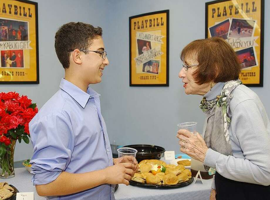 """The Middletown Press) Eighth-grader Warren Hadley, of Durham, looks with Harry Dickerson, of Middletown, at """"Home Front to Frontline,"""" a book Hadley and his classmates produced under the direction of their teachers, Liz Warner and Julia Kleederman, as part of a local history class at the Independent Day School in Middlefield. Muriel Schulman, center, of Middletown, talks with Kleederman. Students interviewed Middletown residents who either served or lived during World War II."""
