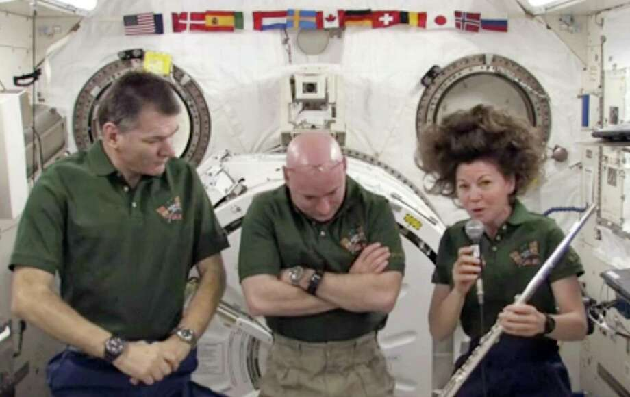 """In this frame grab from video shot on Wednesday, and made available by NASA, astronaut Catherine Coleman, right, holds her flute aboard the International Space Station during an interview. One of the flutes is her own. Two belong to members of the Irish group """"The Chieftains."""" And one belongs to the flutist with the Jethro Tull band. Coleman says she prefers creating music with other people. But she's the only flutist among the six-member space station crew. So she puts flute music on in the background, and plays along. (AP Photo/NASA) Photo: ASSOCIATED PRESS / AP2011"""
