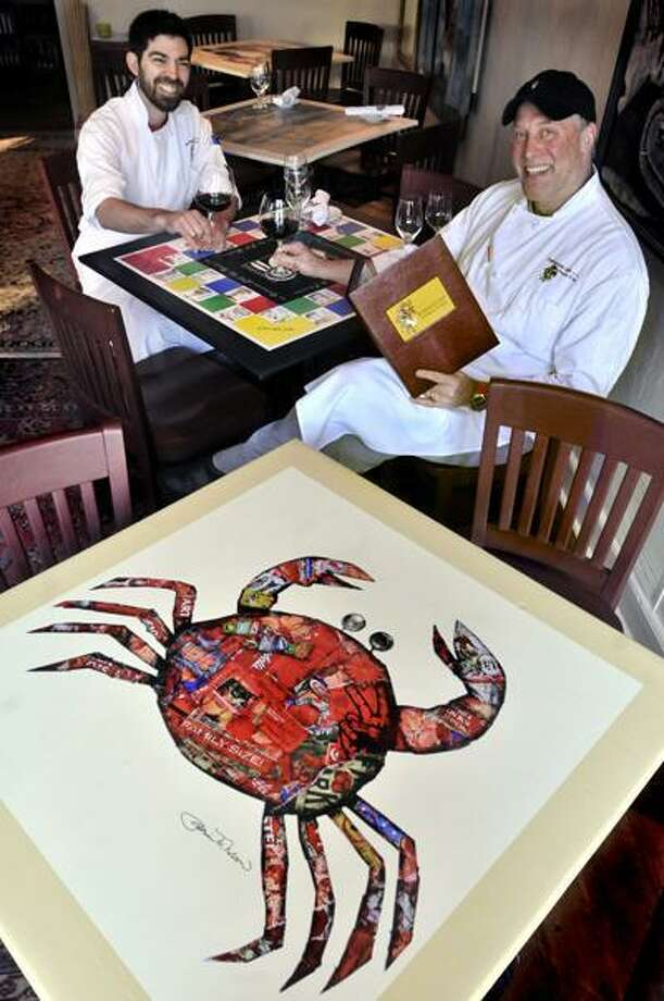 Melanie Stengel/Register photos, Owner Everett Reid, right, and Chef Alejandro Carroll Leiva of Restaurant L&E are surrounded by tablecloths created by Chester artists, including Patrice Nelson, front.