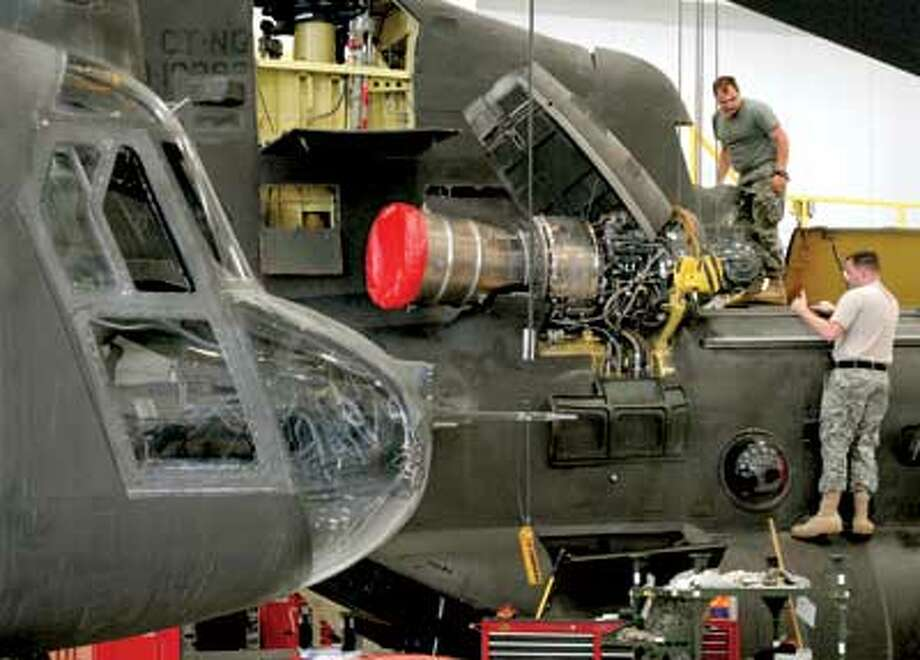 Chinook and Black Hawk helicopters are serviced at the Army Aviation Support Facility in Windsor Locks. BELOW: Guardsman Jerry Santos, right, sets up the simulated firing range at Camp Rell in East Lyme, with help from Guardsman Tom Bordner. (Melanie Stengel/Register)