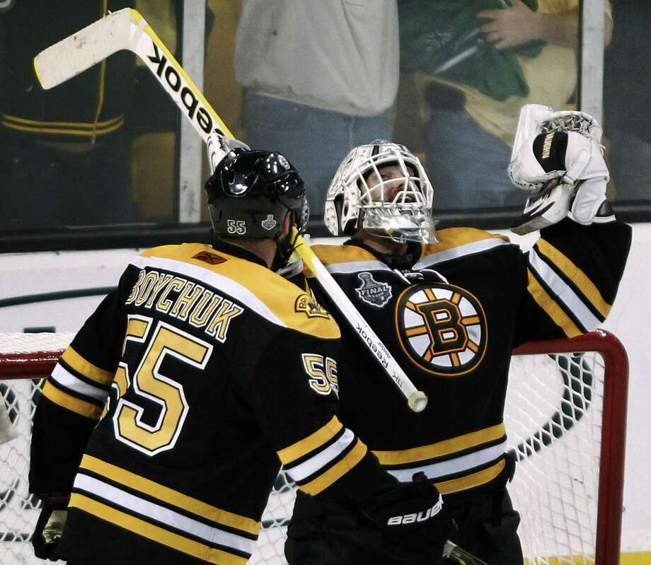 Boston Bruins goalie Tim Thomas, right, reacts with teammate Johnny Boychuck at the end of the Game 4 against the Vancouver Canucks during their NHL hockey Stanley Cup finals, Wednesday, June 8, 2011, in Boston. The Bruins' 4-0 win tied the best-of-seven series at 2-2. (AP Photo/Winslow Townson) Photo: ASSOCIATED PRESS / AP2011