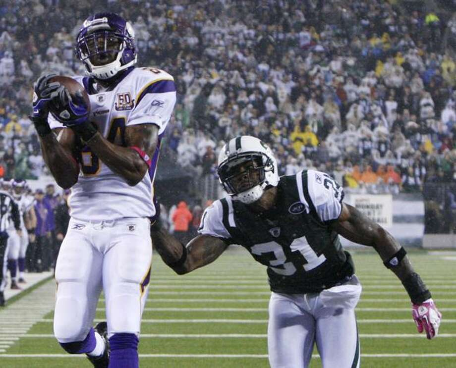 Minnesota Vikings' Randy Moss catches a touchdown pass while covered by New York Jets' Antonio Cromartie during the third quarter of an NFL football game  Monday in East Rutherford, N.J. (AP Photo/Seth Wenig) Photo: AP / AP