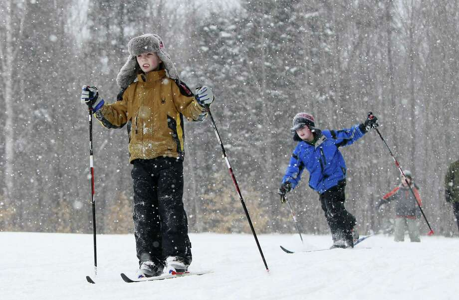 In this photo taken Thursday, third grader Aidan Brown, left, and classmates cross country skis during a physical education class at the New Sweden Consolidated School in New Sweden, Maine. Students from the first grade on up ski on groomed trails in the woods just behind the elementary school. (AP Photo/Robert F. Bukaty) Photo: ASSOCIATED PRESS / AP2011