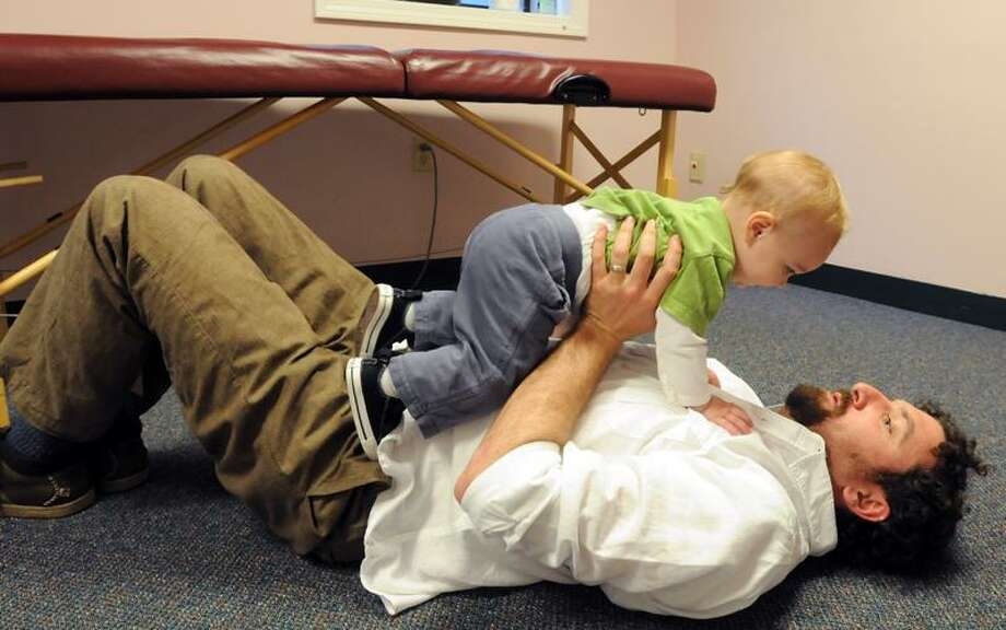 """UP: In his medical offices naturopath Joshua Levitt hoists friend Raleigh Harwell age 14 months of Hamden to demonstrate one of his """"baby barbells"""" exercises. (Mara Lavitt/Journal Register News Service)"""