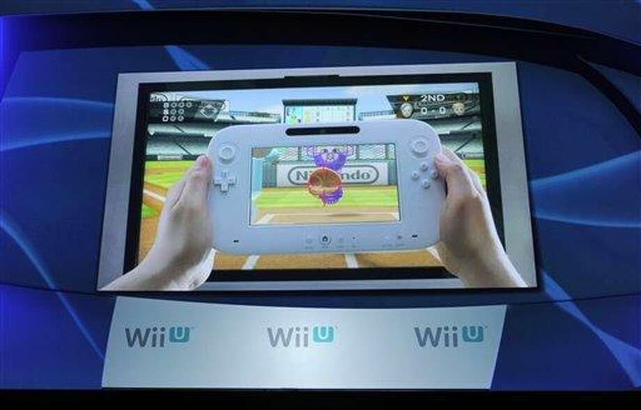 The new Nintendo Wii U gaming console is displayed on a video screen during a news conference at the E3 Gaming Convention in Los Angeles, Tuesday. (AP Photo/Chris Pizzello) Photo: AP / AP