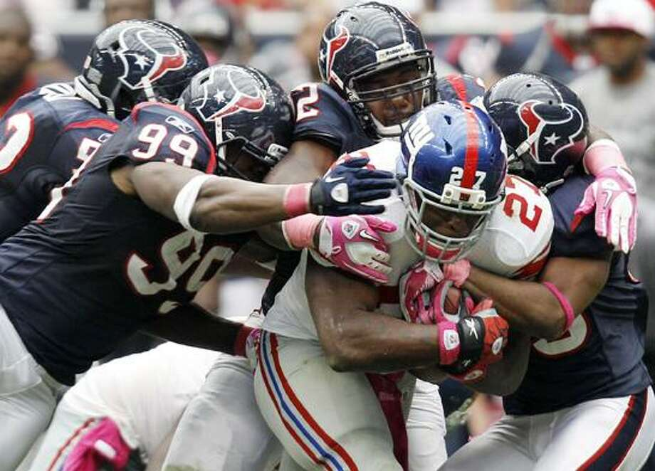 New York Giants' Brandon Jacobs (27) pulls along four Houston Texans defenders, including Adewale Ogunleye (99), in the fourth quarter of an NFL football game Sunday in Houston. The Giants won 34-10. (AP Photo/Eric Gay) Photo: AP / AP