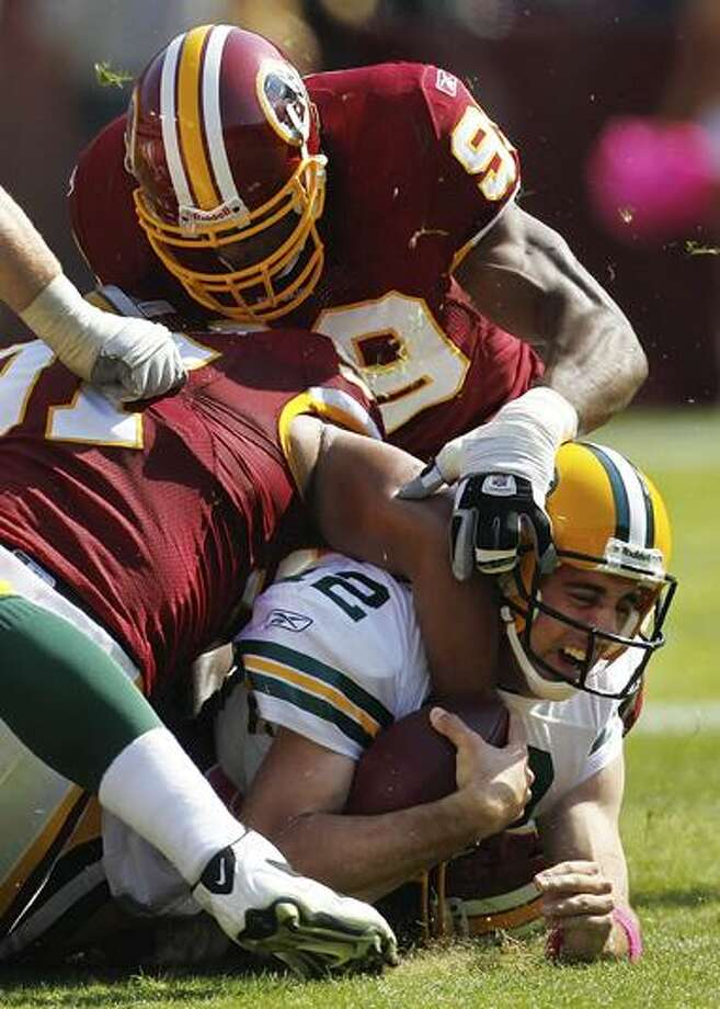 Washington Redskins linebackers Lorenzo Alexander, left, and Andre Carter sack Green Bay Packers quarterback Aaron Rodgers during the first half of an NFL football game in Landover, Md., Sunday. Washington won 16-13 in overtime. (AP Photo/Pablo Martinez Monsivais) Photo: AP / AP