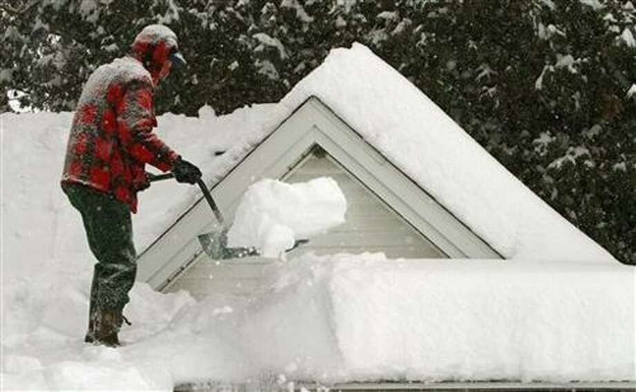 FILE - In this Feb. 2, 2011 file photo, Harry Eastman shovels the snow off his garage roof in Barre, Vt.  Doctors across the battered Northeast are seeing a spike in strained muscles from shoveling snow, broken bones from slick stairs and sidewalks, and dangerously low blood banks as fewer people venture out. (AP Photo/Toby Talbot, File) Photo: AP / AP2011