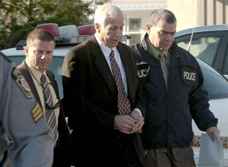 """FILE - In this Nov. 5, 2011 file photo provided by the Pennsylvania Office of Attorney General, former Penn State football defensive coordinator Gerald """"Jerry"""" Sandusky, center, walks to the office of Centre County Magisterial District Judge Leslie A. Dutchcot while being escorted by Pennsylvania State Police and Attorney General's Office officials in State College, Pa. A lawsuit was filed against him Wednesday. (AP Photo/Pennsylvania Office of Attorney General via Commonwealth Media Services, File) Photo: ASSOCIATED PRESS / AP2011"""