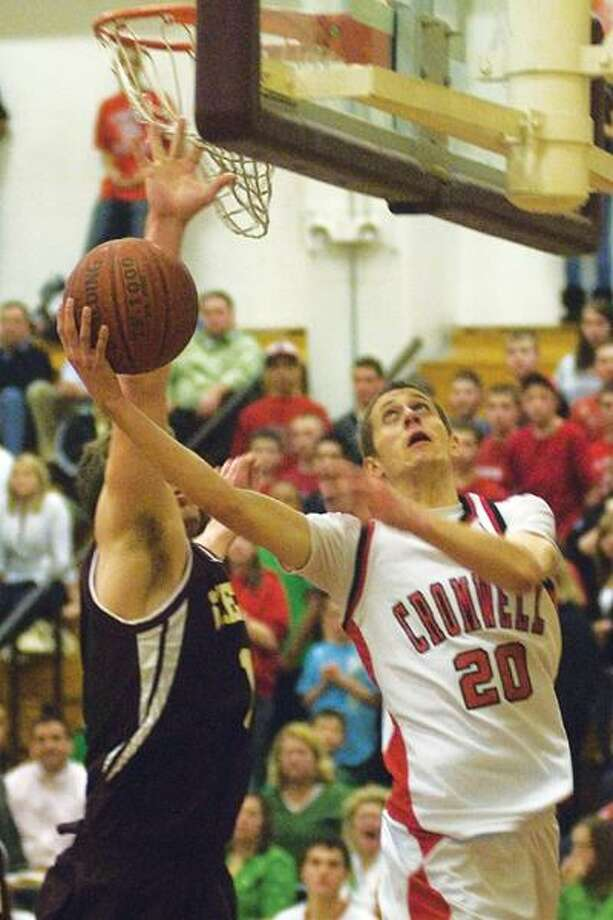 Cromwell's Matt Burns goes in for a layup as Sheehan's Brett Biestek defends Wednesday in the Class M semifinals. (Max Steinmetz / Special to the Press)