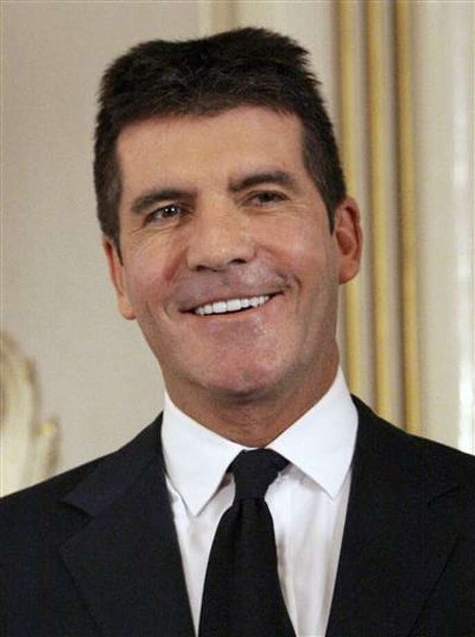 FILE- In this June 6, 2010 file photo, British music mogul Simon Cowell holds his honorary Bafta Award, during the British Academy Television Awards at the London Palladium in central London. (AP Photo/Joel Ryan, file) Photo: AP / AP2010