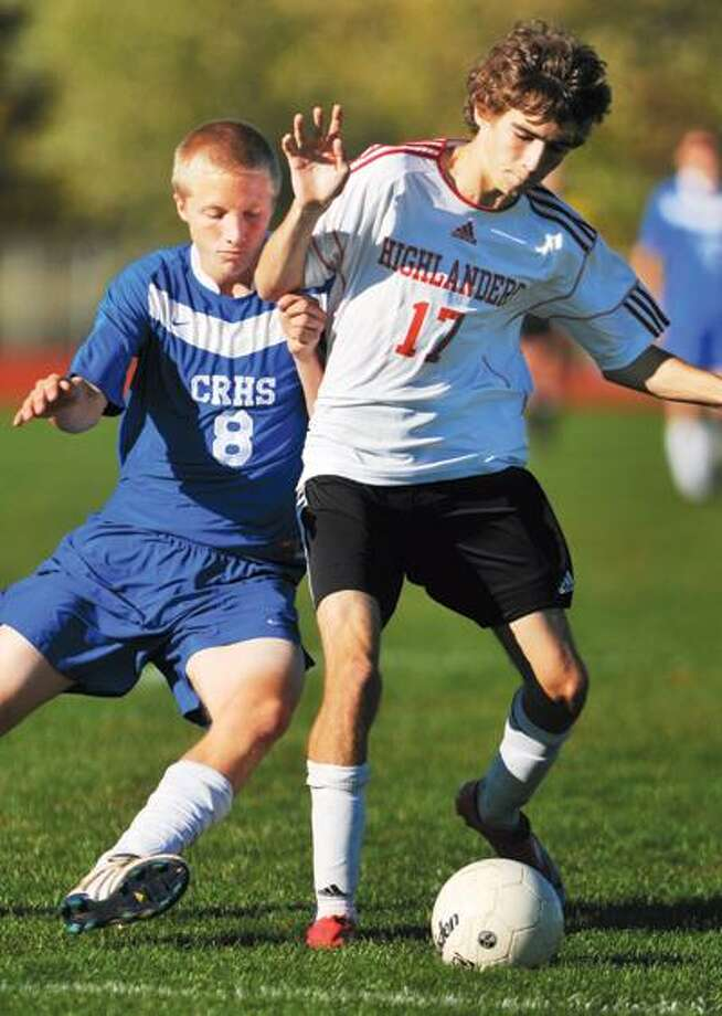Portland's Zane Lombardo is challenged by Coginchaug's Matt Schock during a home match ending in a win for the Highlanders Friday.(Catherine Avalone / TheMiddletownPress