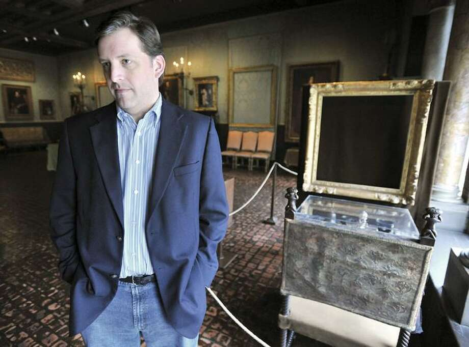 """In this Thursday, March 11 photo, Anthony Amore, current security director at the Isabella Stewart Gardner Museum in Boston, stands beside empty frames from which thieves took """"The storm on the Sea of Galilee,"""" center rear, by Rembrandt and """"The Concert,"""" right front, by Vermeer. The paintings were among more than a dozen works stolen from the museum in 1990 in what is considered the largest art theft in history. It remains the most tantalizing art heist mystery in the world. In the early hours of March 18, 1990, two thieves walked into Boston's elegant Isabella Stewart Gardner Museum disguised as police officers and bound and gagged two guards using handcuffs and duct tape. For the next 81 minutes, they sauntered around the ornate galleries, removing masterworks including those by Rembrandt, Vermeer, Degas and Manet, cutting some of the largest pieces from their frames. Now, 20 years later, investigators are making a renewed push to recover the paintings. (AP) Photo: AP / FR25426 AP"""